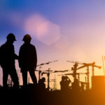 silhouette of two construction workers standing in front of a construction site with a purple, yellow sky.